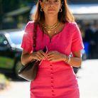 Une robe rose fuchsia avec des bijoux dorés