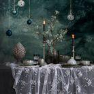 Une déco de table de Noël qui parie sur la nappe en dentelle et les boules de Noël suspendues