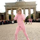 il pose dans une combinaison rose avec un sexe rose apparent