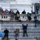 Dehors, les manifestants grimpent pour tenter de s'infiltrer dans la bâtisse